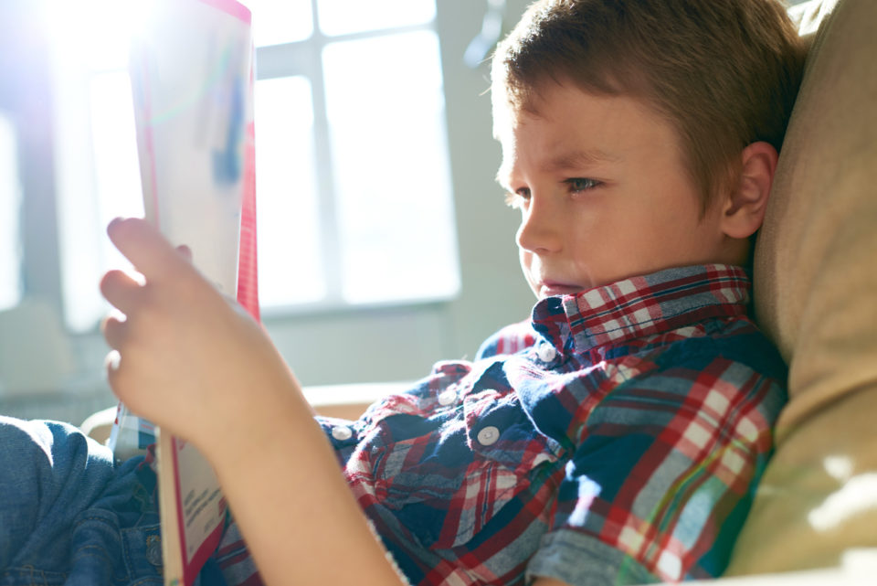 Side view of relaxing boy reading magazine