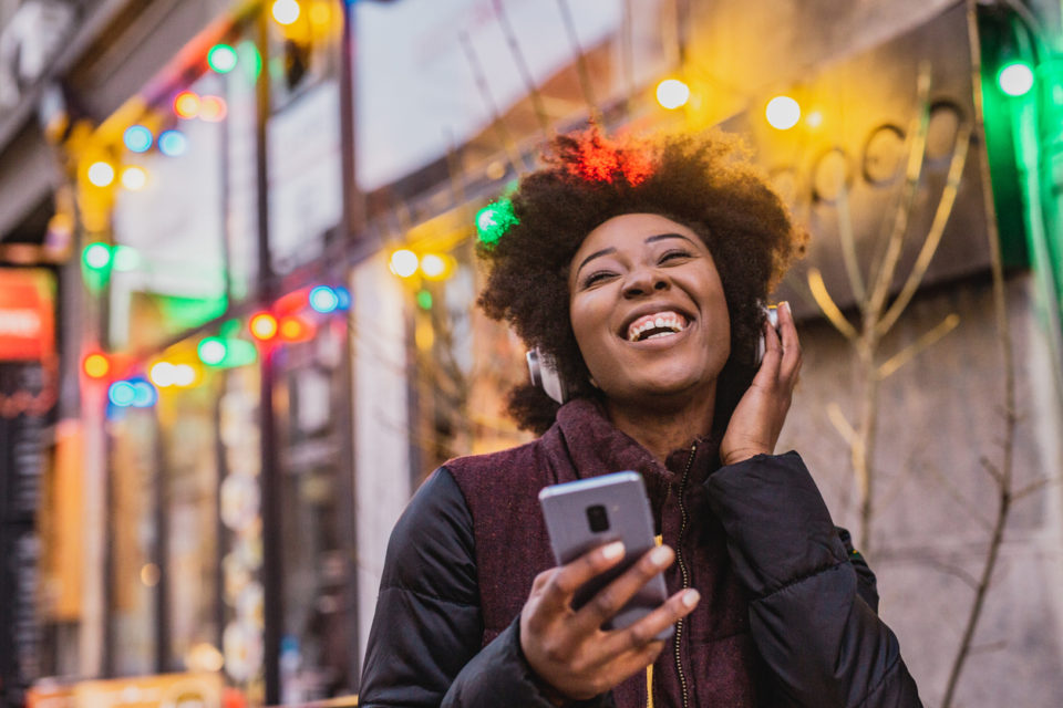 A young woman is using a mobile phone and wireless headphones outdoor during Christmas