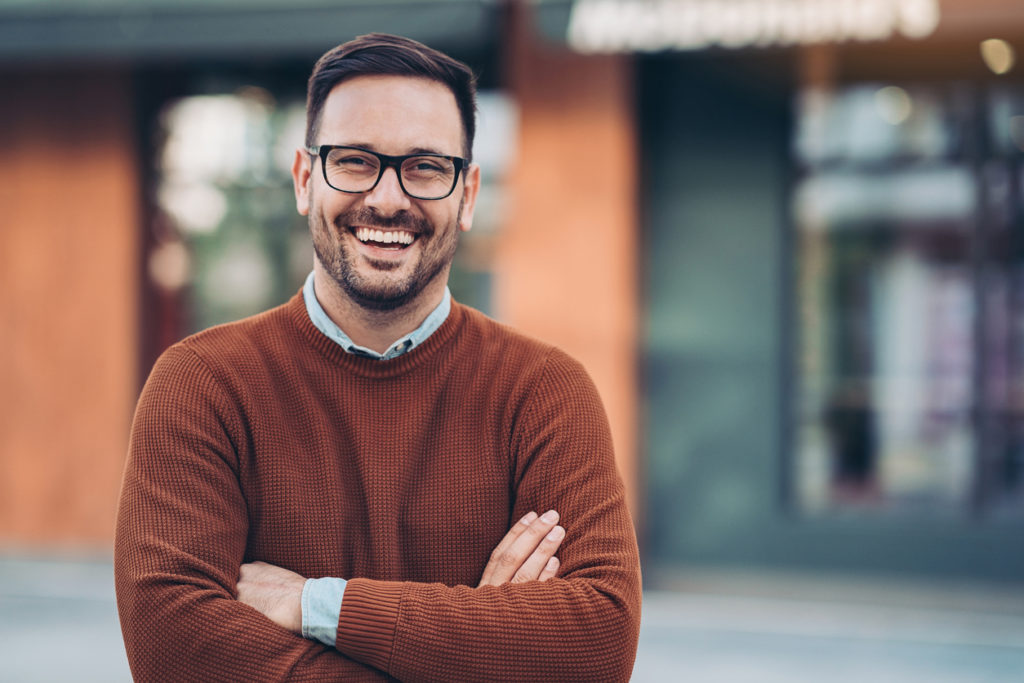 Smiling man outdoors in the city wearing orange sweater.